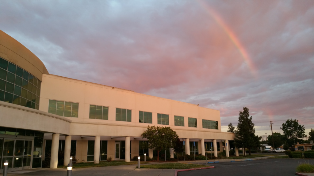 A photo taken at dusk, Serna Center building, front side, with a red sky peeking through clouds, and a rainbow trying to get through.